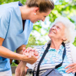 Nurse holding hand of senior woman in pension home