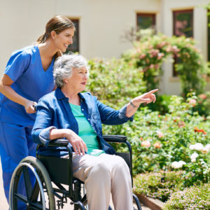 Shot of a resident and a nurse outside in the retirement home garden