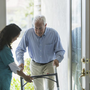 A home healthcare worker, a mature woman of Pacific Islander ethnicity, helping a senior man with a walker enter his house through the front door. She is holding the walker, directing him to watch is step.
