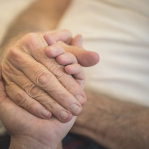 A stock photo of a young woman holding the hands of her Elderly Father who is receiving home hospice care. Photographed using the Canon EOS 1DX Mark II