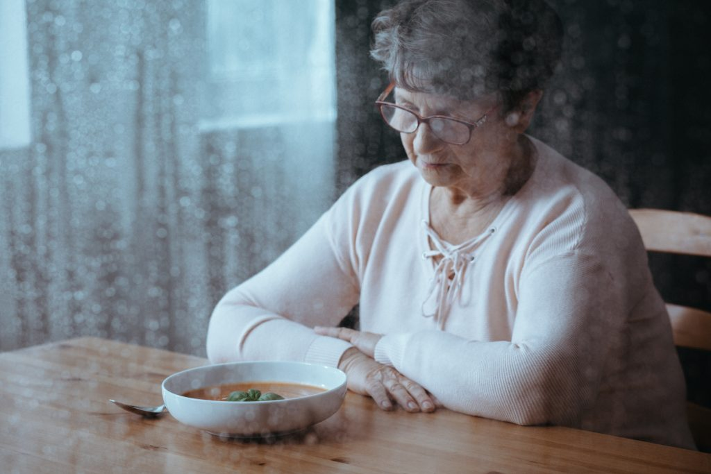 Unhappy senior woman looking at a bowl of soup with no appetite.